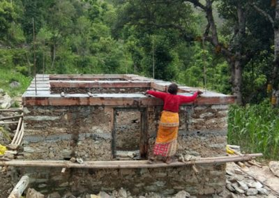 A woman working to rebuild her house-Ramechhap.