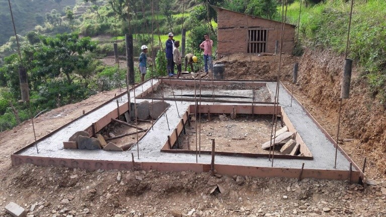 Ongoing construction of EQ resilient house next to temporary shed